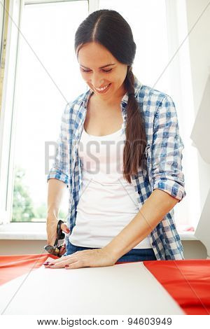 smiley woman cutting red fabric with tailors scissors