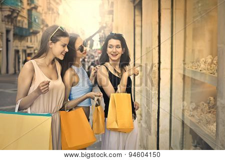 Three beautiful girls window shopping in the city