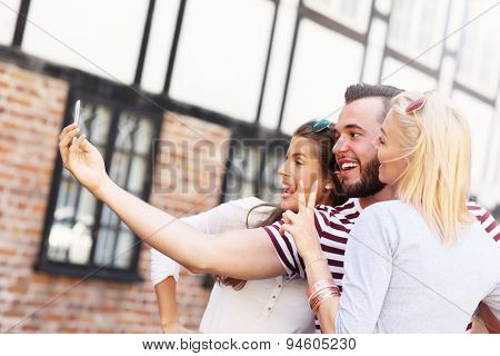 A picture of a group of happy friends taking selfie in the city