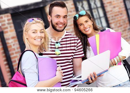 A picture of a group of happy students studying outdoors