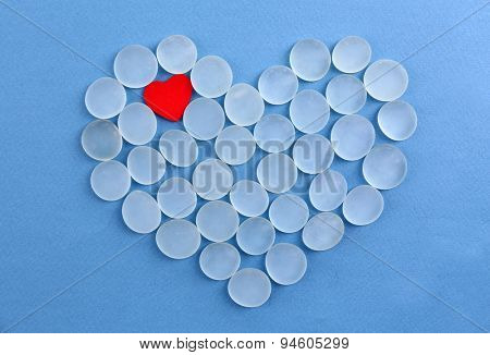 Decorative stones in heart shape on blue background