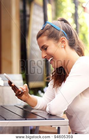 A picture of a happy woman using smartphone in cafe