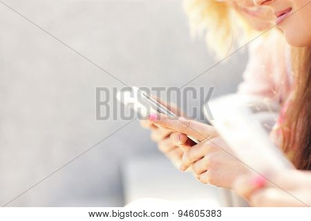 A picture of a group of girl friends using smartphones