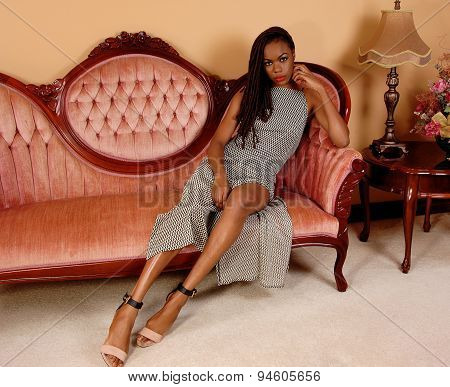 Pretty African Woman On Pink Couch.