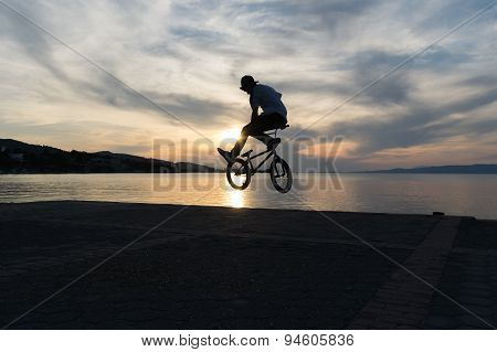 Bmx tricks against a dramatic sky.