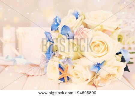 Beautiful wedding bouquet with sea decor on wooden table