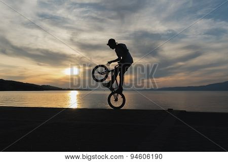 Biker jumping with the sunset as background.