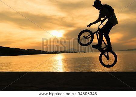 Bmx biker tricks against a beautiful sunset.