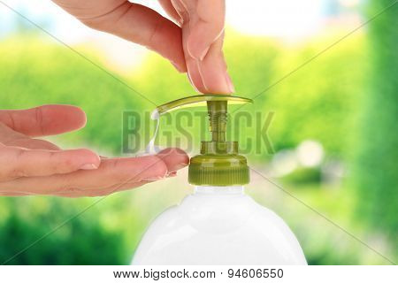 Female hands using liquid soap on nature background