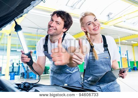Mechanic team working in car workshop