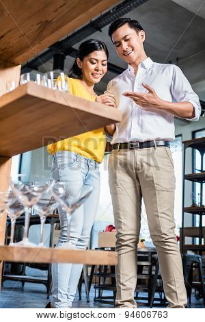 Couple in furniture store choosing glasses, Asian woman and Caucasian man