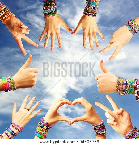 Female hands with bracelets on sky background