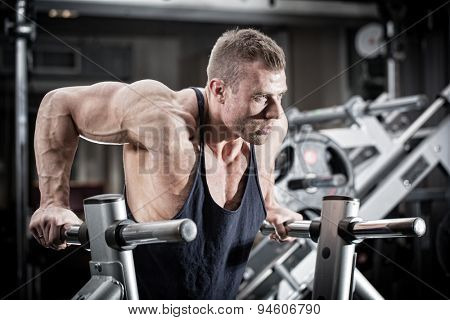 Bodybuilder man in gym doing dips as arm training