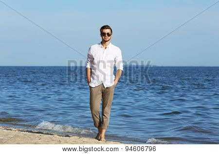 Young man walking on beach