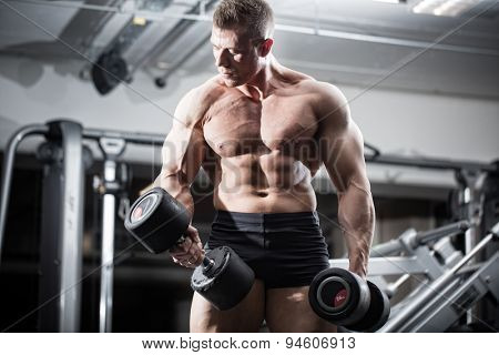 Bodybuilder in gym at fitness training with barbells standing in front of equipment