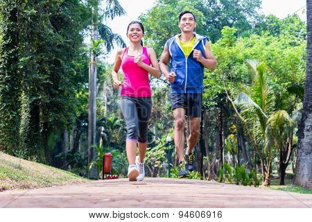 Asian couple, man and woman, jogging or running in tropical Asian park for fitness