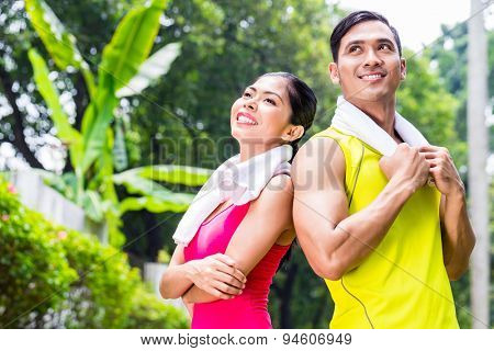 Asian woman and man during jogging training standing shoulder to shoulder with towels