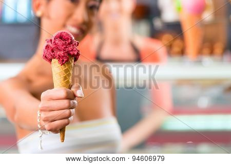 Young female customer in an ice cream parlor with ice cream cornet