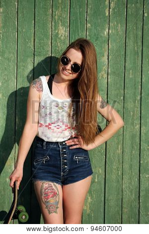 Beautiful girl with tattooed body, holding skateboard on wooden wall background