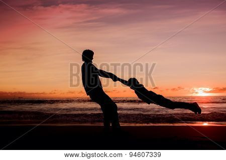 Silhouettes of father spinning his son around on sunset