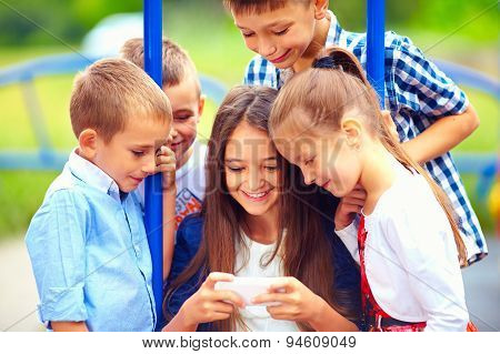 Group Of Happy Kids Playing Online Games Together, Outdoors