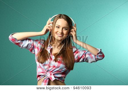 Young woman with headphones on turquoise background