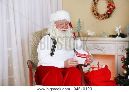 Santa Claus sitting with children presents in comfortable chair near fireplace at home