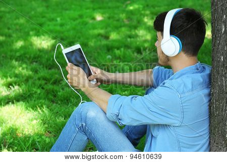 Man with headphones resting under tree in park