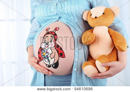 Beautiful young pregnant with baby toy  and picture on her belly, on light background