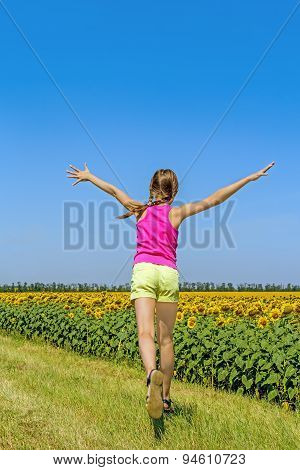 Girl Running Along The Field With Sunflowers