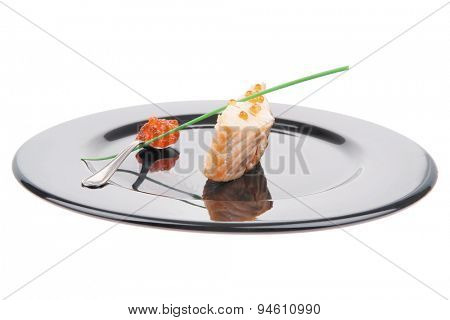 diet food : baked pink salmon steaks with green onion and red caviar in spoon on black dish isolated over white background