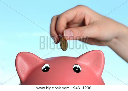 Hand inserting money into piggy bank on blue background