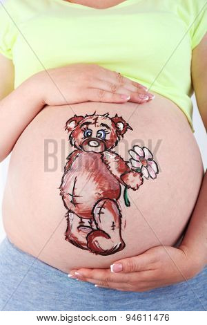 Body art on belly of pregnant woman on light background