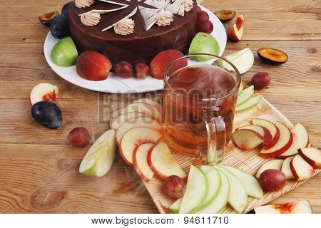 big whole frost chocolate cream brownie cake topped with white chocolate and cream flowers with hot tea cup decorated with fruits apple plum and grape on plate on wooden table