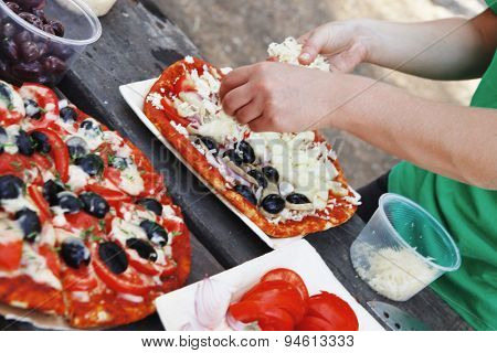 prepare hand made pizza with olives and tomatoes on wooden table on picnic with different kind of cheeses