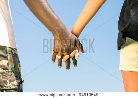 Multiracial Couple Walking Hand In Hand Against A Blue Sky - Concept Of Multi Ethnic Love