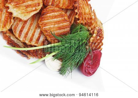 potato chips served with small pickled eggplants on small white plate isolated on white background