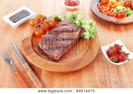 fresh rich juicy grilled beef meat steak fillet with marks on wooden plate over table decorated with lettuce salad and cutlery, new york styled cuisine