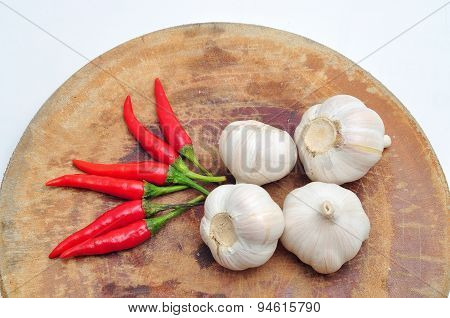Chili and garlic on the cutting board in a white background