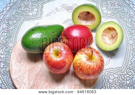 Fruits of avocado and apple on the cutting board