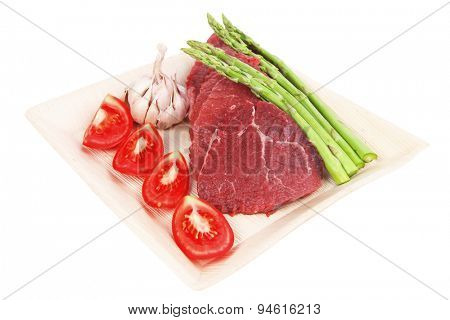 fresh raw beef meat steak fillet on wooden plate with asparagus and tomatoes ready to prepare isolated over white background