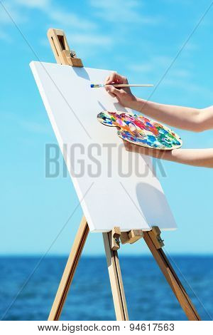 Female hand holding palette with paints and easel with canvas on beach
