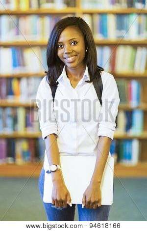attractive female african college student holding laptop