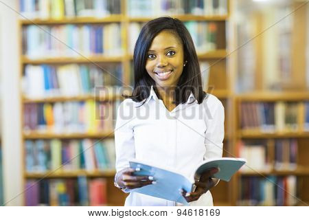 cheerful african college student reading a book in library