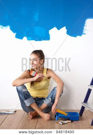 Portrait of female painter sitting on floor after painting.