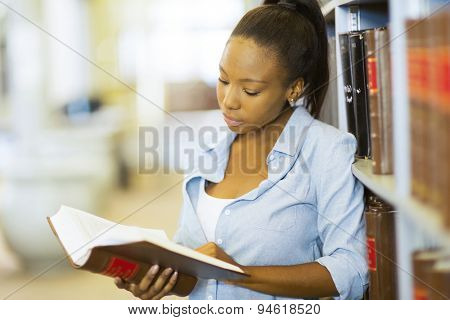 young female african university student reading a book in library