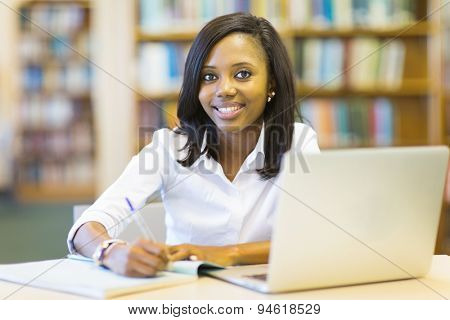 beautiful afro american student sitting in college library