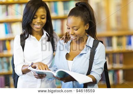 cheerful african college girls reading a book in library