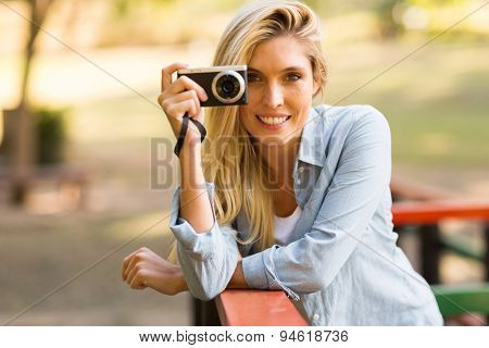 beautiful blond woman taking photos in the nature
