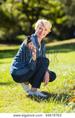 cheerful senior woman holding a camera outdoors